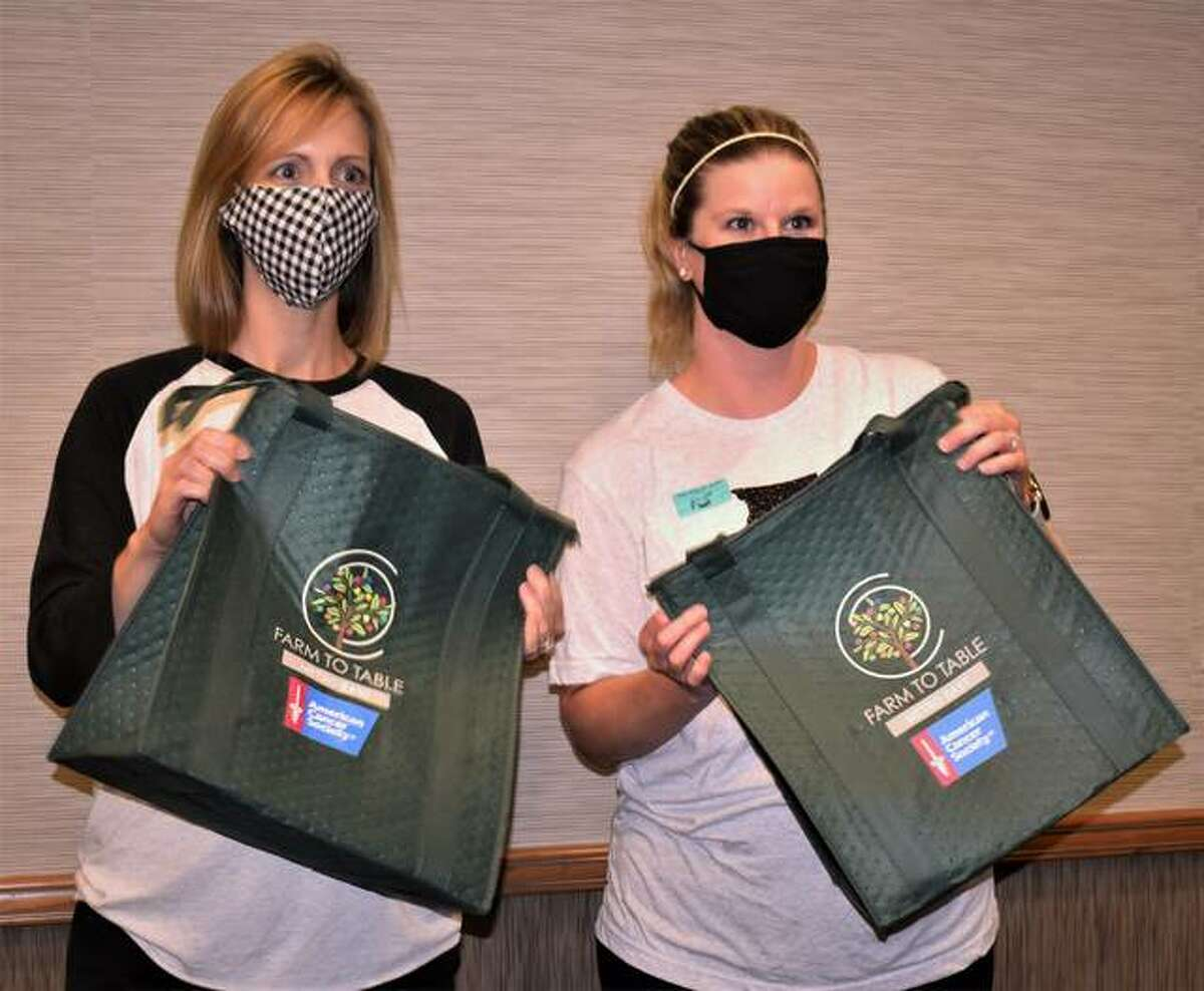 """Volunteer Alissa Fuhrmann, left, a staff person for last year's Farm to Table Metro East event when she was employed with the American Cancer Society (now employed with AdvantaClean) and on the current Farm to Table committee as its vendor lead, and ACS' Sheena Whitehead, right, senior development manager, help hand out Farm to Table Metro East totes at last year's first """"to-go"""" event. This year the event also features a DIY option as well as a """"Food and Beverage"""" option, but this year Troy blogger Rachel Tritsch, of Recipes with Rachel, provided an easy-to-prepare recipe."""