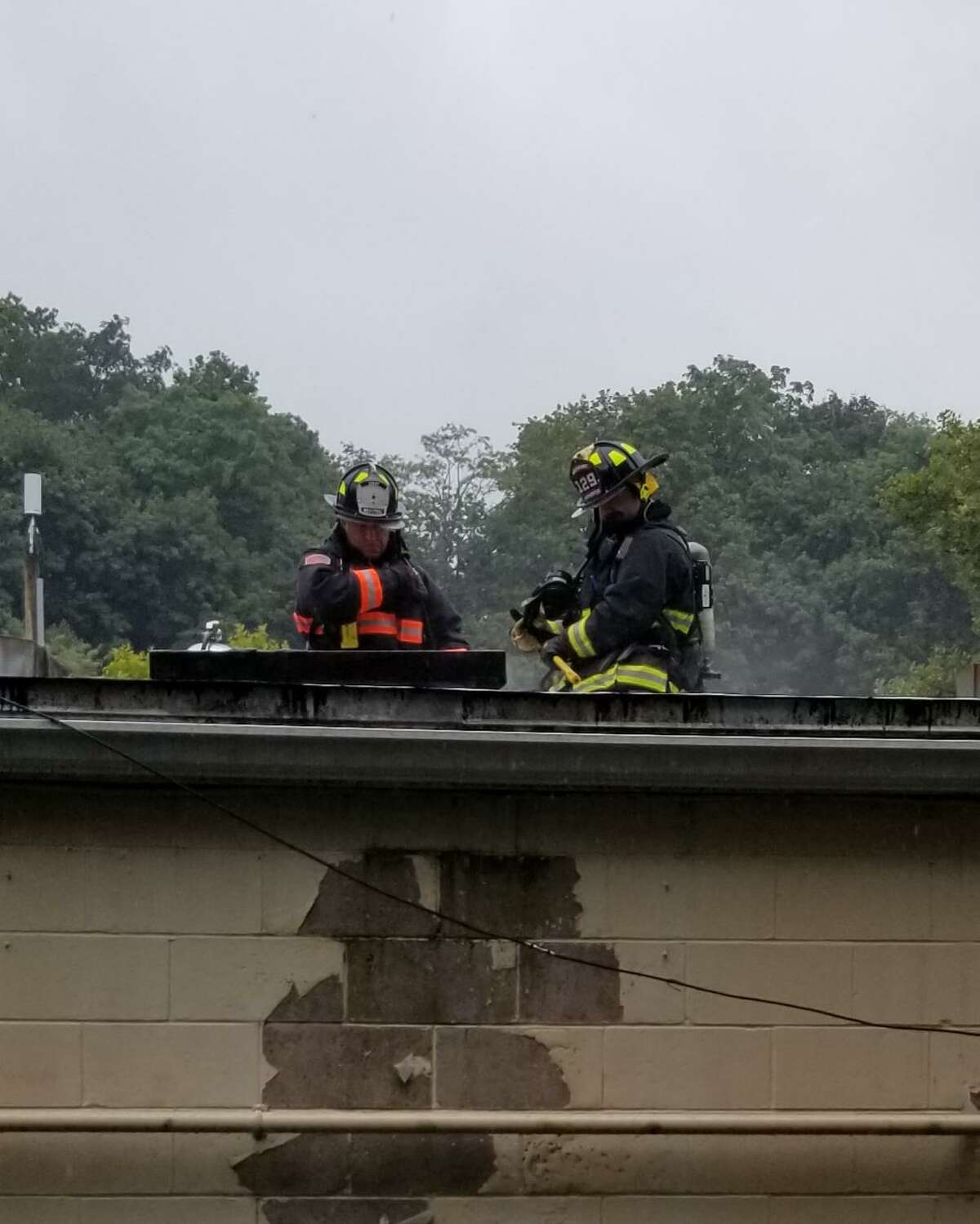 Crews work to extinguish a roof fire at a commercial building in Westport, Conn. Monday, Aug. 9, 2021