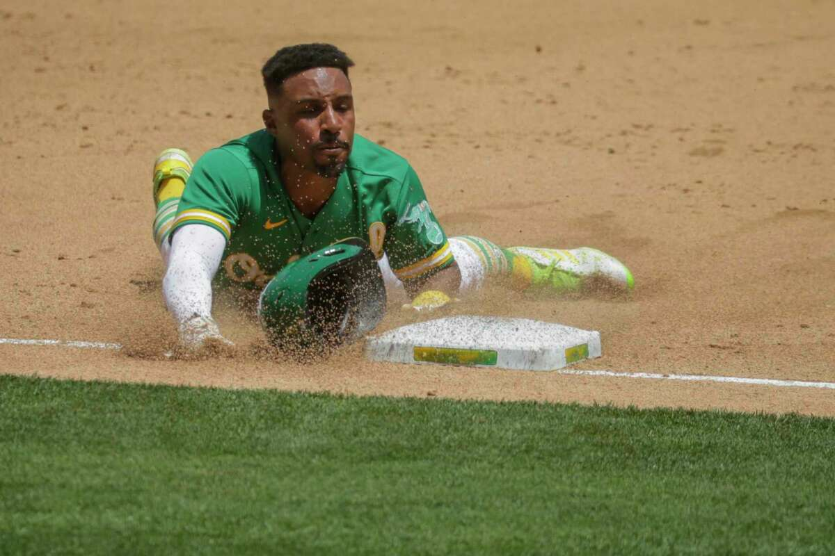 Tony Kemp (5) slides to third during the bottom of the fifth inning as the Oakland Athletics played the Los Angeles Angels at the Coliseum in Oakland, Calif. Wednesday, June 16, 2021. The A?•s defeated the Angels 8-4.