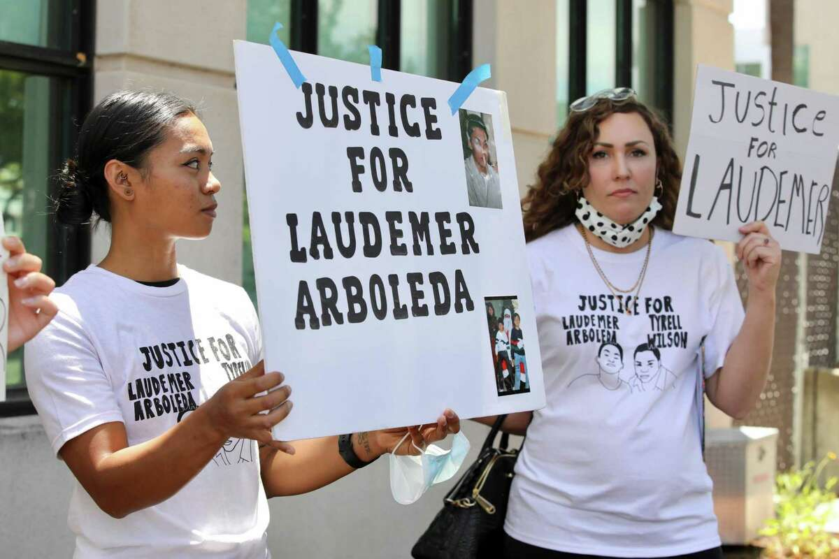 Irina Lukban, left, of Danville, an activist with Conscious Contra Costa, holds a sign following an arraignment hearing for Danville police Officer Andrew Hall outside the A.F. Bray Courthouse on Wednesday, June 16, 2021, in Martinez, Calif. (Yalonda M. James / The Chronicle)