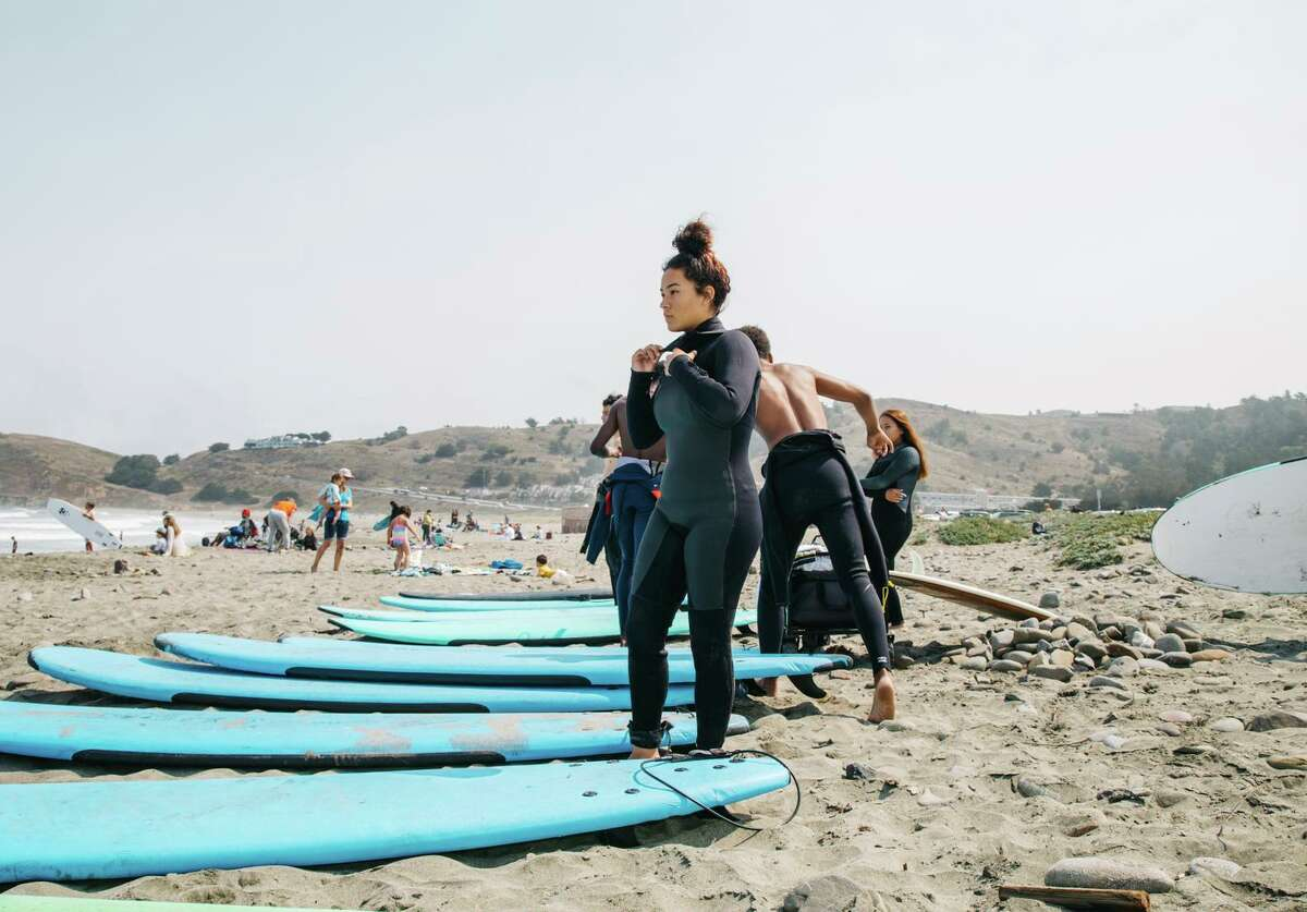 Angely Lopez, an instructor for City Surf Project, prepares to go out at Linda Mar Beach in Pacifica.
