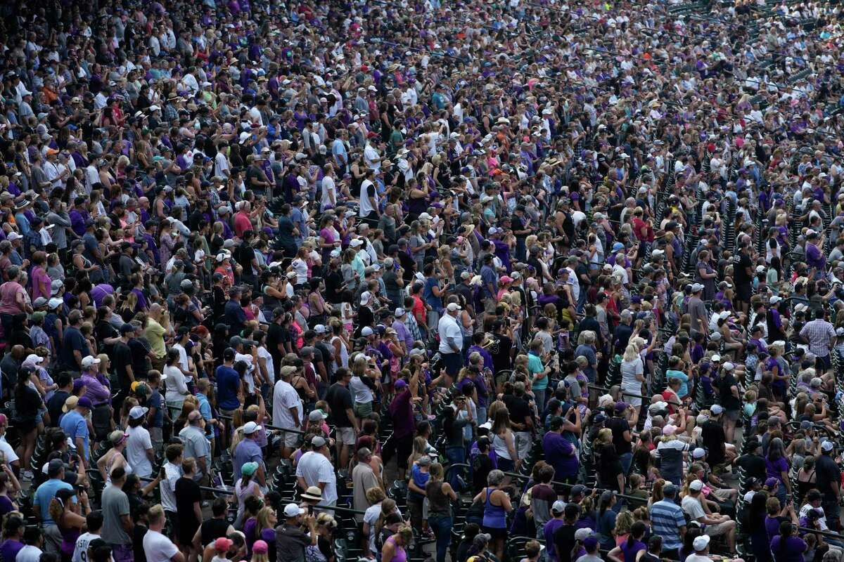 Fans crowd into the box seat along the third-base line of Coors Field to listen to a Christian rock group perform as part of a faith day promotion after the ninth inning of a baseball game Sunday, Aug. 8, 2021, in Denver. The Colorado Rockies defeated the Miami Marlins 13-8. (AP Photo/David Zalubowski)