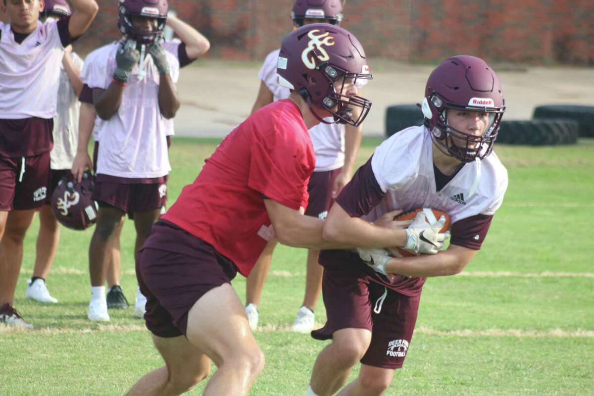 Quarterback Teague Sedtal gets the football securely into the arms of a running back during Monday's first day of workouts.