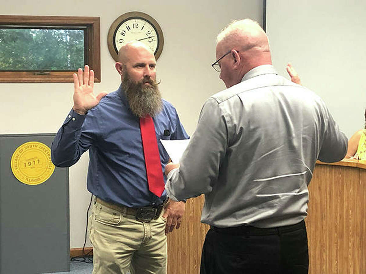 South Jacksonville Police Chief Eric Hansell was reinstated as chief Monday evening after village trustees voted to overturn Hansell's termination. Hansell (left), recites an oath with Mike Broaddus in front of a full house at village hall.