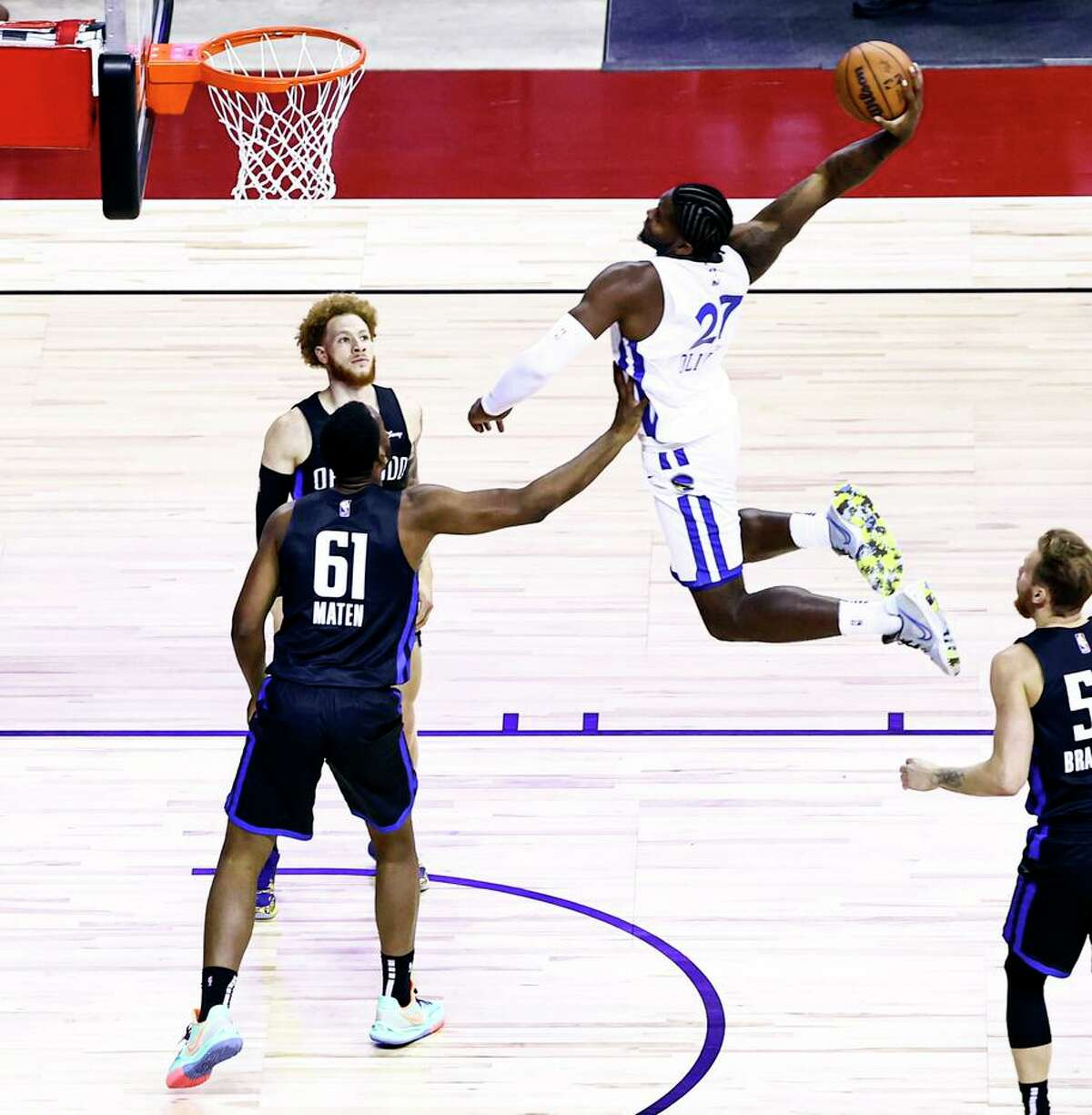The Warriors' Cameron Oliver leaps for a dunk against the Orlando Magic's Yante Maten (61) and Hassani Gravett.
