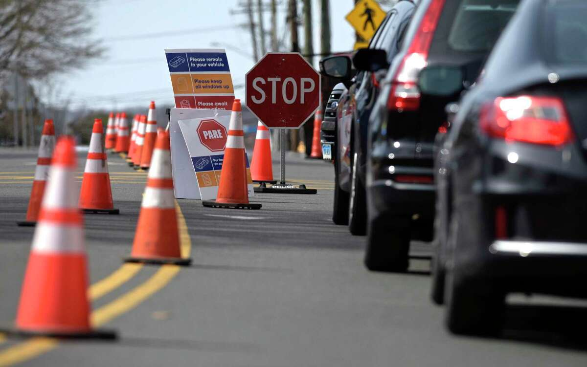 Cars wait in line at a drive-thru testing site for COVID-19 in Danbury, March 2020. This week, New Milford will offer not only free COVID-19 tests but also vaccines.