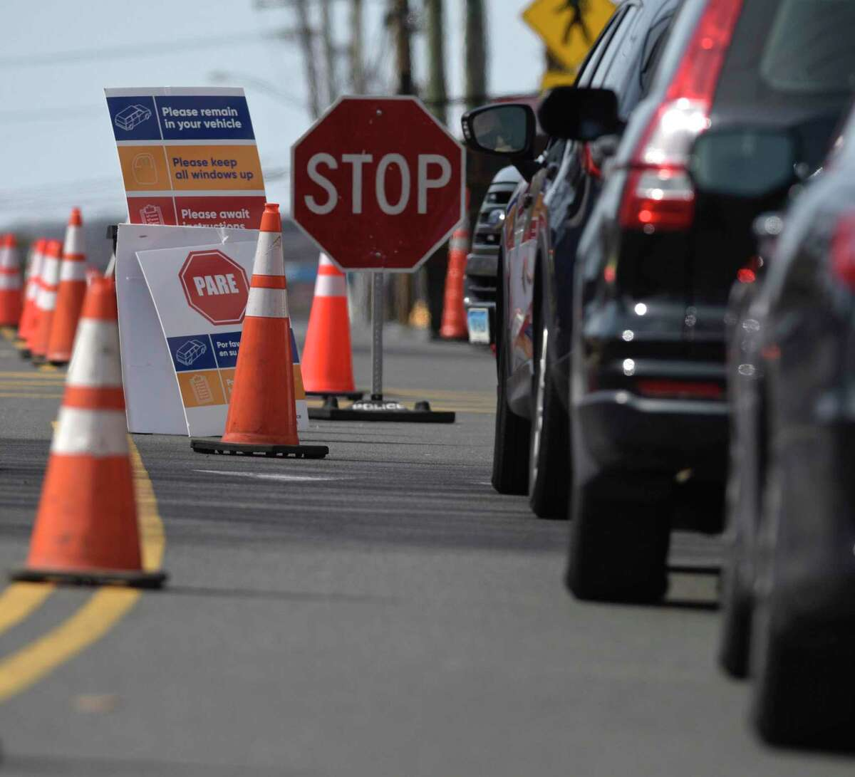 Cars wait in line at a drive-thru testing site for the respiratory virus known as COVID-19 that has been setup in one of Danbury Hospitals parking garages. The Danbury Police Department is controlling the flow of traffic to the street. Wednesday, March 18, 2020, in Danbury, Conn.