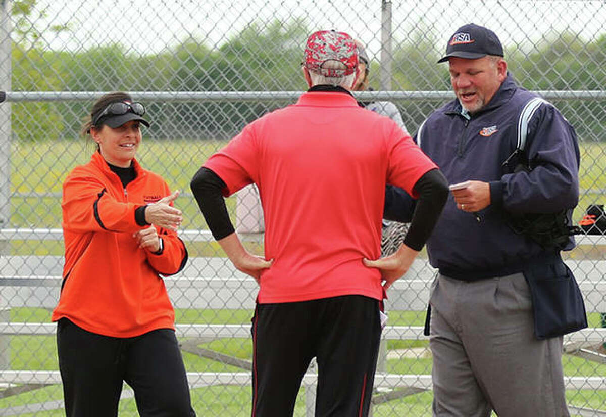 Gillespie coach Michelle Smith (left) reaches out to greet Highland coach Glenn Nicholls before meeting with plate umpire Dave Bishop (right) before a May game in Gillespie.