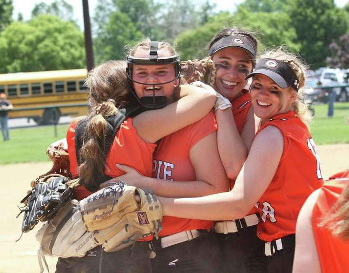 Gillespie's Sydney Bires (second left) is embraced by teammates after throwing a shutout to beat Marquette Catholic in the title game of the Marquette Class 2A Regional on June 5 at Moore Park in Alton.