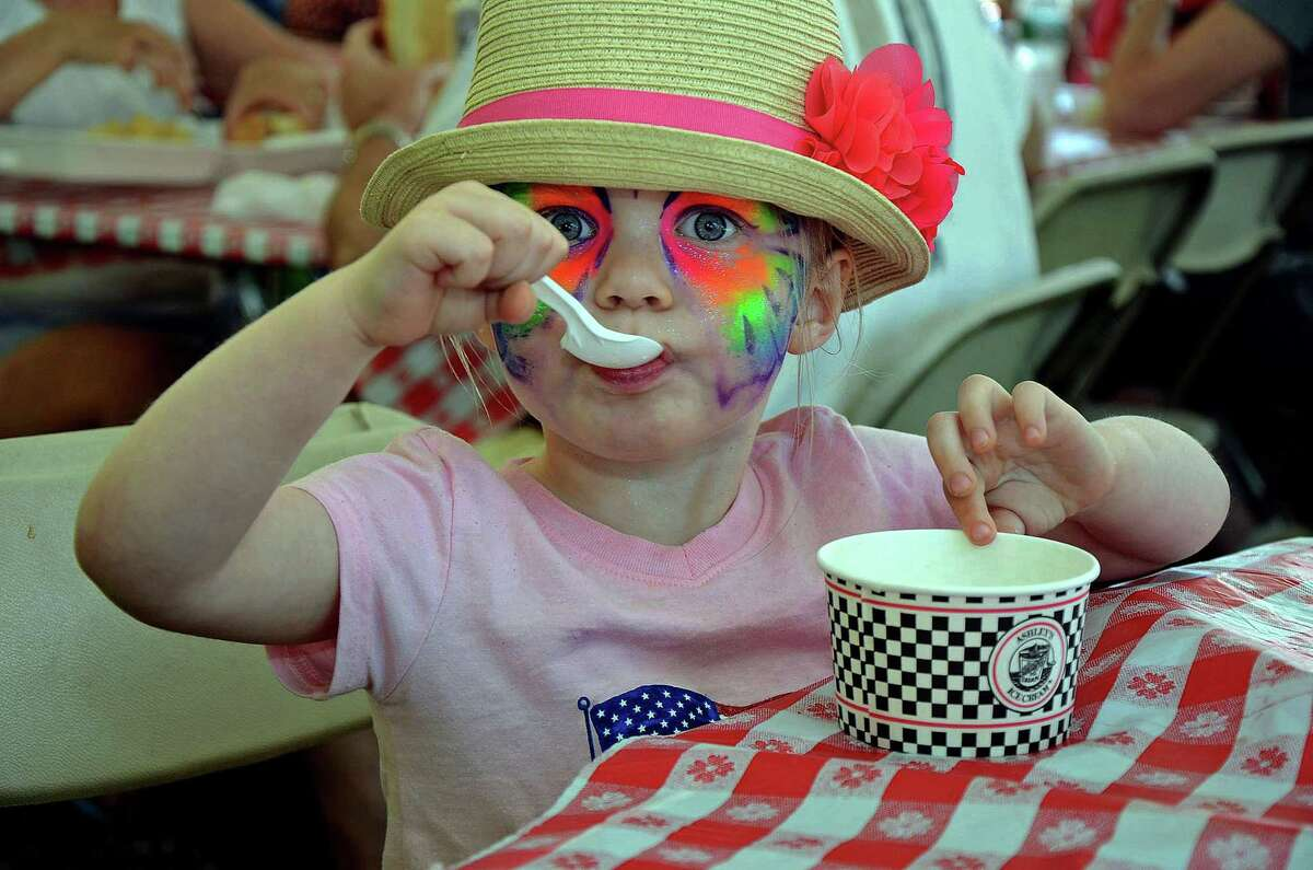 Face painted girl enjoying the sweetness of the Branford Festival.