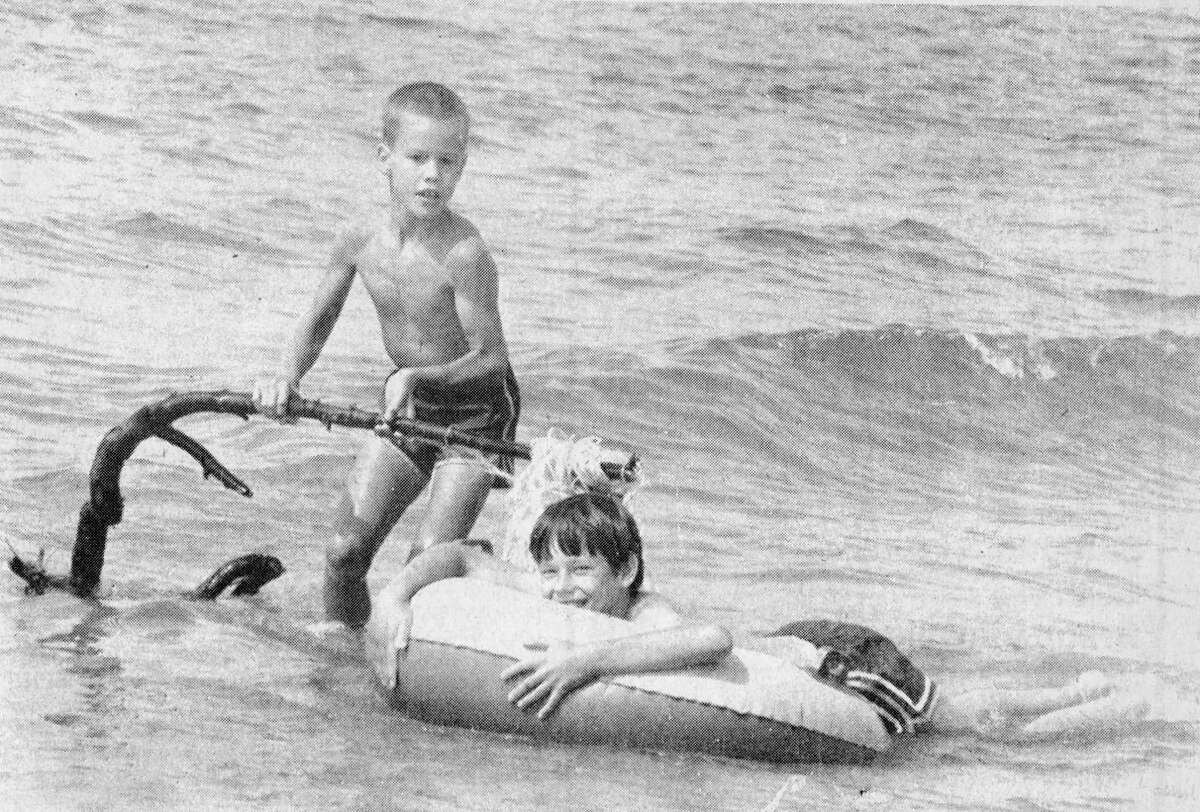 (From left) Josh Turbyville and Steve O'Rourke were caught rollicking in the waves of Lake Michigan yesterday afternoon, a popular local August activity. Enjoy it while you can, kids - the toll of the schoolhouse bell will be heard in another three weeks, and it'll be back to the classrooms. The photo was published in the News Advocate on Aug. 11, 1981. (Manistee County Historical Museum photo)