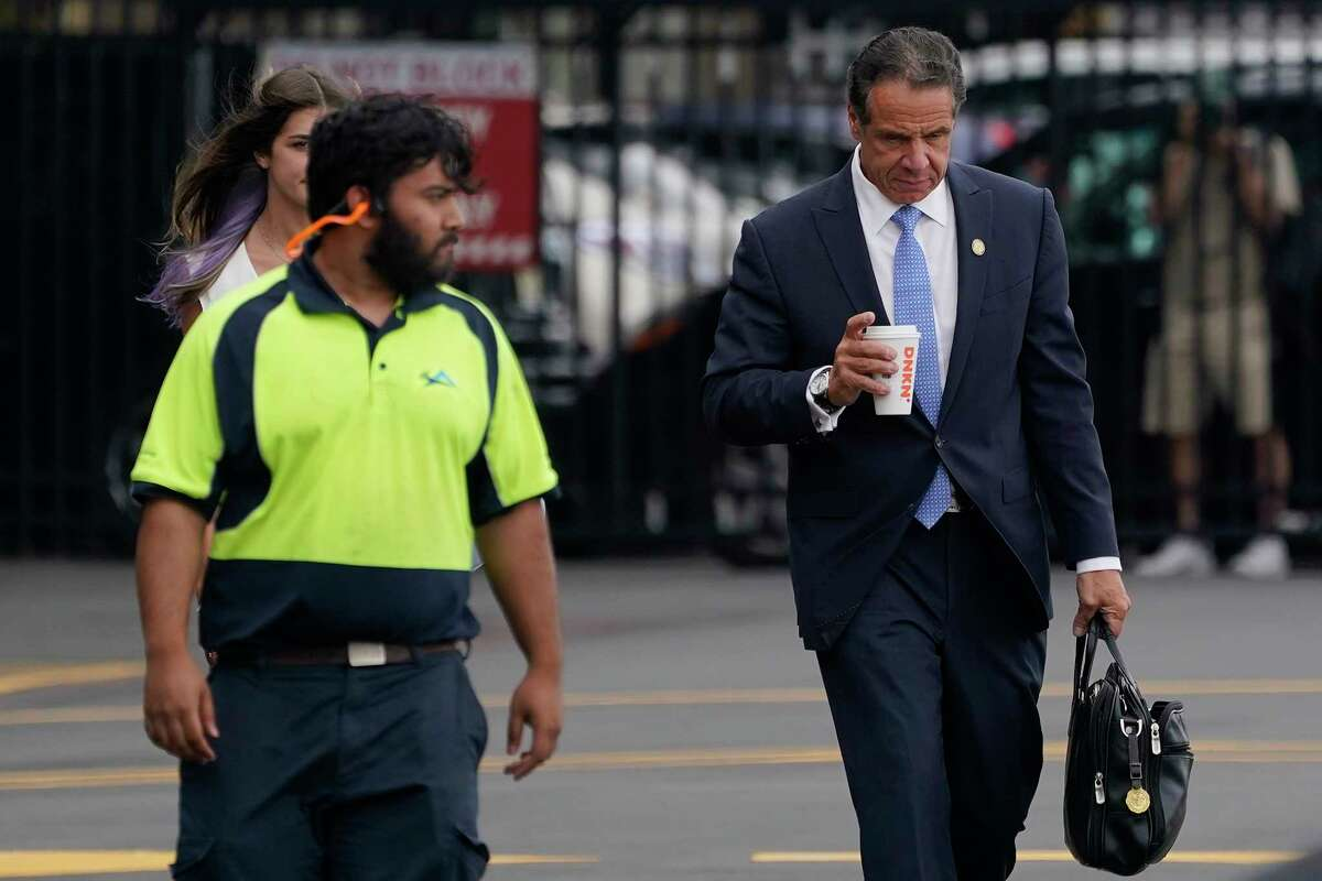 New York Gov. Andrew Cuomo, right, prepares to board a helicopter after announcing his resignation, Tuesday, Aug. 10, 2021, in New York. Cuomo says he will resign over a barrage of sexual harassment allegations. The three-term Democratic governor's decision, which will take effect in two weeks, was announced Tuesday as momentum built in the Legislature to remove him by impeachment.