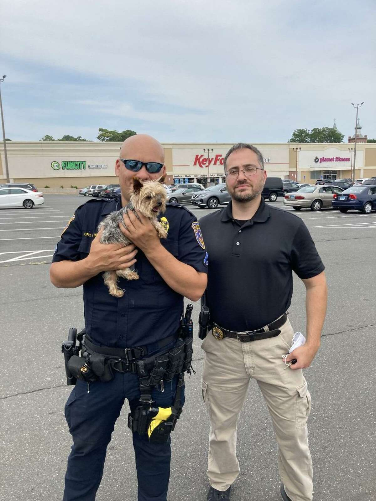 Cookie with Meriden, Conn., police after he was reunited with his owners. The dog was stolen out of his owners' yard on Aug. 4, 2021, before being listed online for sale. An undercover officer recovered the dog.