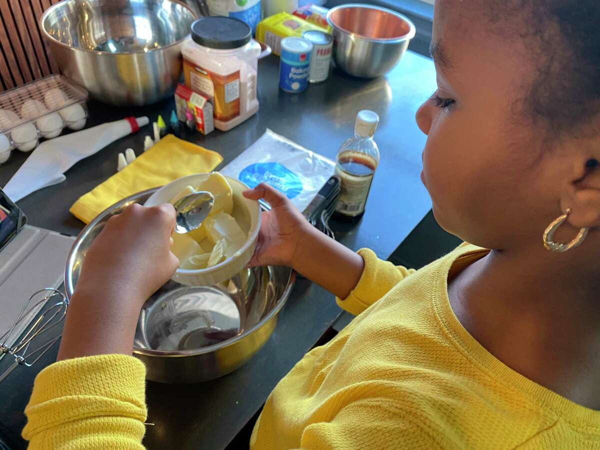 """Asherah Douglass, 9, bakes a pound cake with her mother, Melani, for the National Museum of Women in the Arts's """"Reclamation"""" exhibition."""