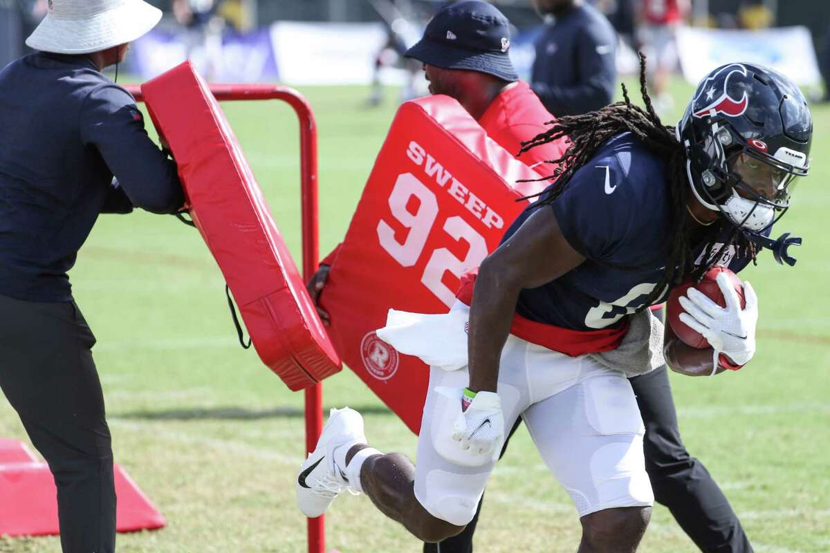 Houston Texans running back Buddy Howell (8) breaks through a pair of blocking pads as he runs a drill during an NFL training camp football practice Tuesday, Aug. 10, 2021, in Houston.