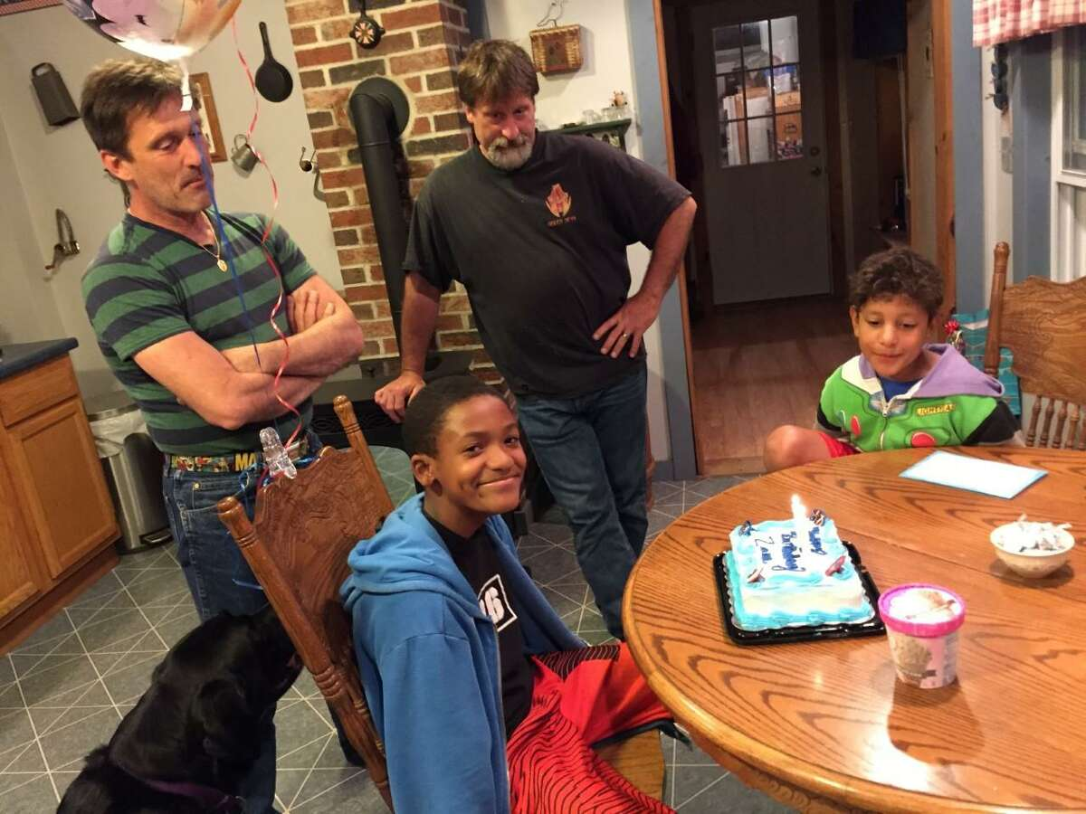 Zane Fisher-Paulson, left, at the table with brother Aidan, celebrates his 13th birthday with dad Brian, Uncle Craig and Aidan in the background.