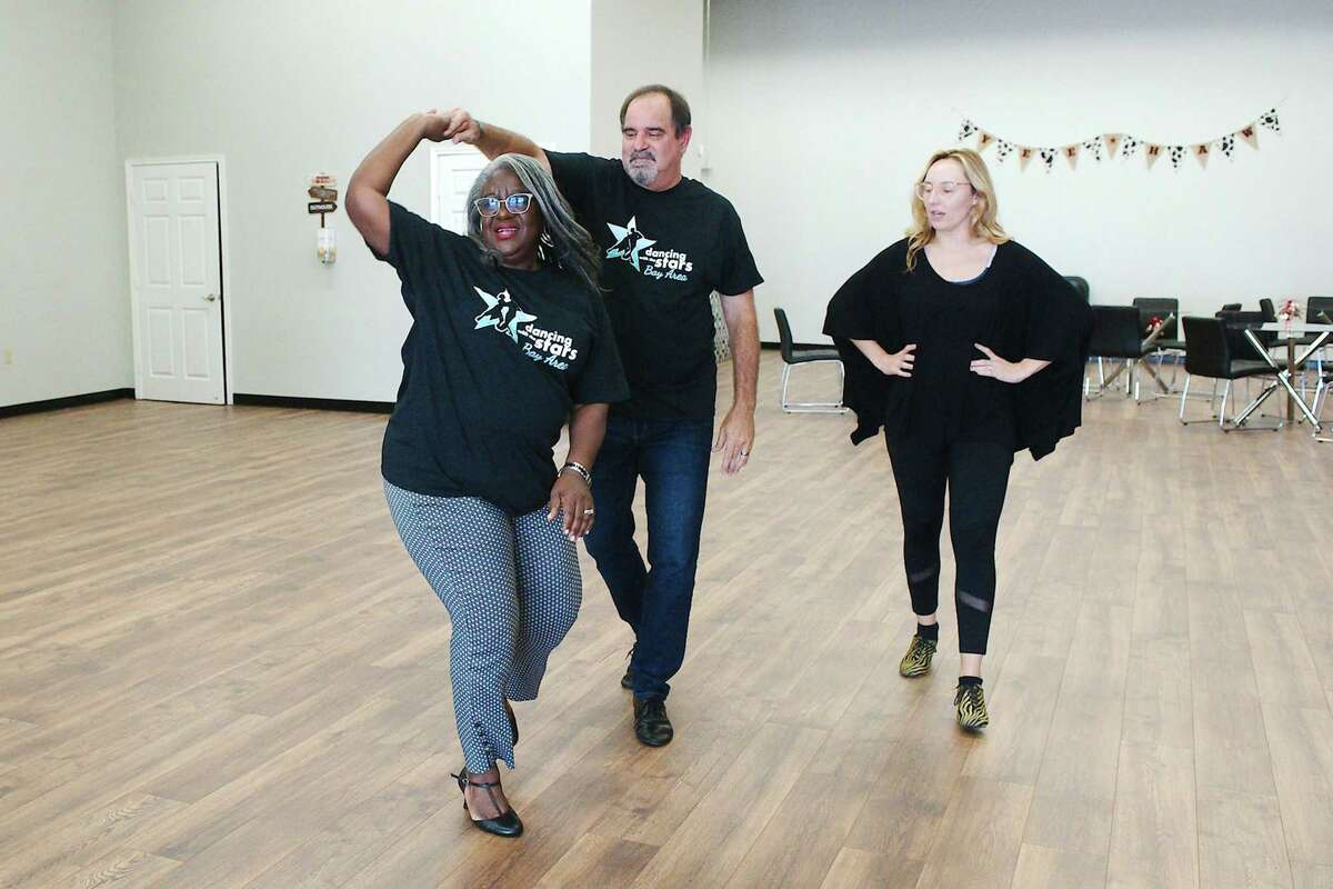 Dance Vision Studios co-owner Mariel Blain watches as Nassau Bay Assistant City Manager Mary Chambers and partner Jay Coppock, chief operating officer for Associated Credit Union of Texas, practice spin moves as they prepare for Dancing with the Stars-Bay Area.