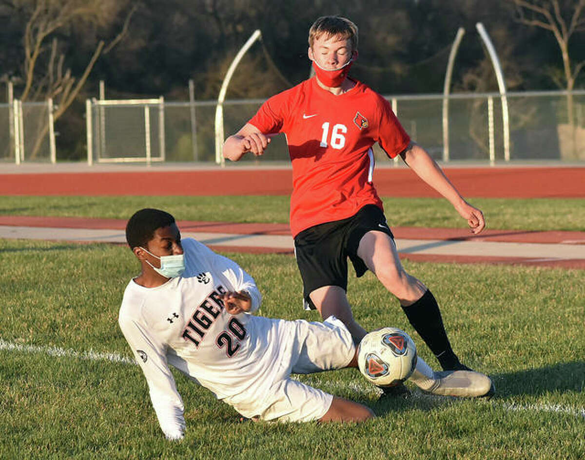 Edwardsville's Chris Agwuedu attempts to tackle the ball away from Alton's Joel Krueger as he makes a pass to a teammate deep in his own zone last season.