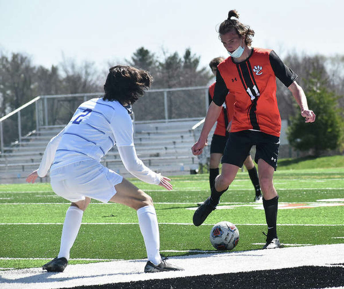 Edwardsville's Ben Mathews, right, looks to make a move past Marquette's Isaac Hendrickson in the first half of a game last season in Edwardsville.