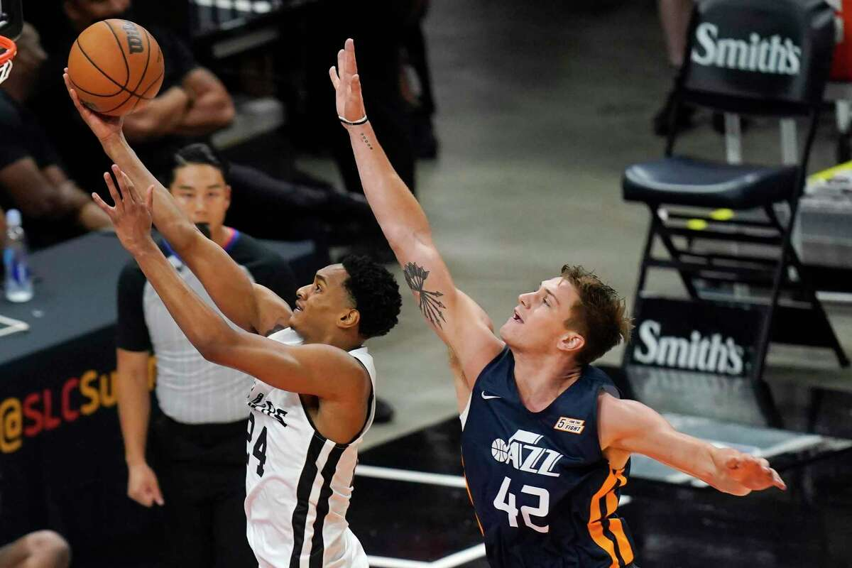 San Antonio Spurs' Devin Vassell (24) goes to the basket as the Utah Jazz's Nate Sestina (42) defends during the first half during an NBA Summer League game Wednesday, Aug. 4, 2021, in Salt Lake City.