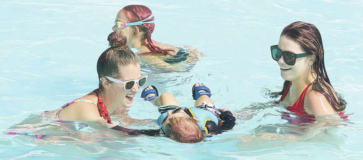 Lauren Cunningham, left, who was visiting friends in the area from Arkansas, on Tuesday was teaching her son, Abel, 2, to float in the water while her friend, Kristen Johnson, right, was there to help. - John Badman|The Telegraph