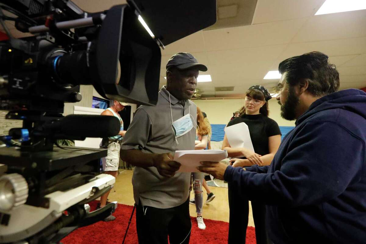 """Charles O'Bryant, center, works over a script with director Santiago Acosta as film students finish filming on their first film """"Escape from Film School"""" at the Indie Film Foundation Studio, Saturday, July 31, 2021, in Conroe."""