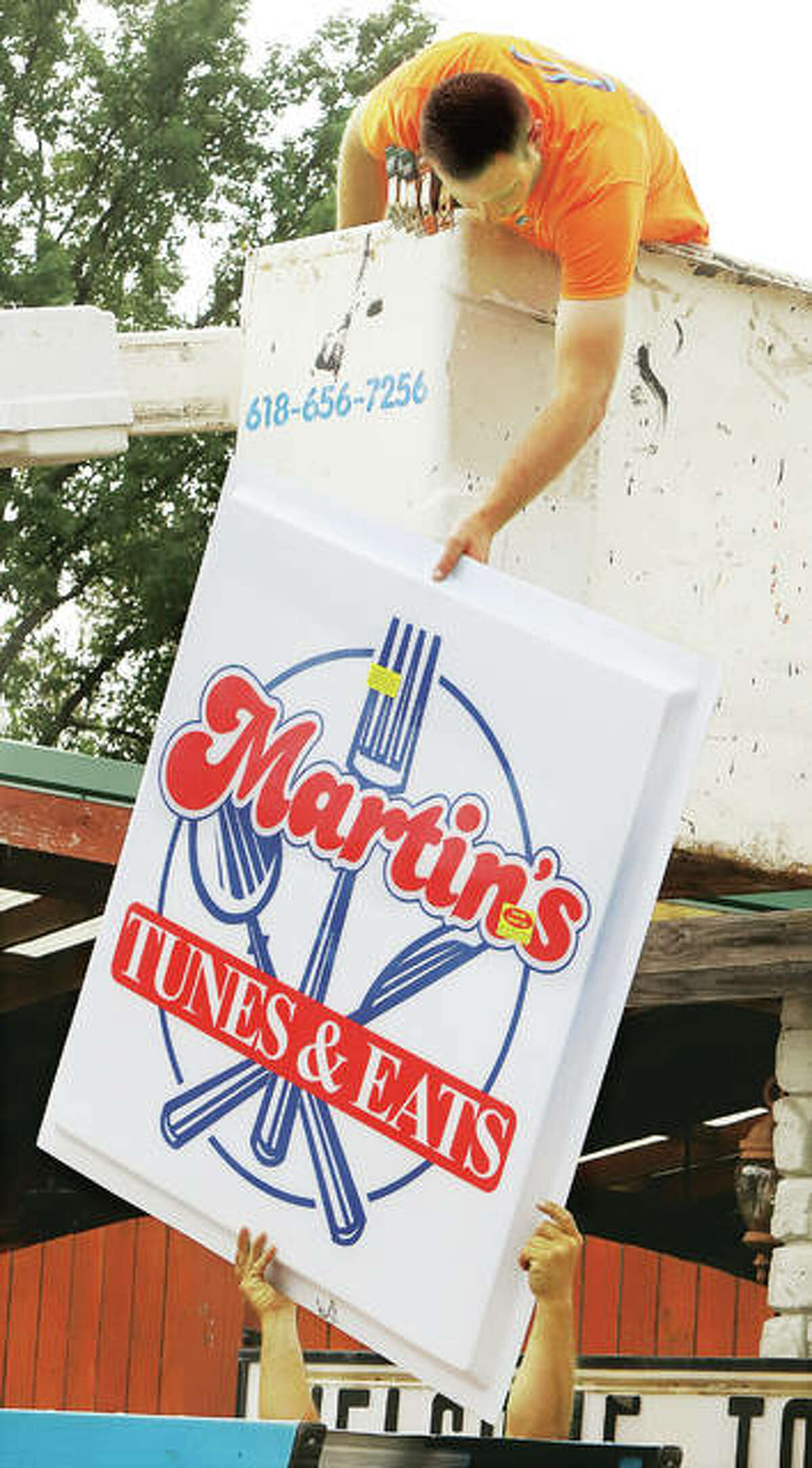 An employee of Eberhart Sign and Lighting prepares to put up the new Martin's Tunes & Eats sign where the former Chico's sign once appeared. - John Badman|The Telegraph