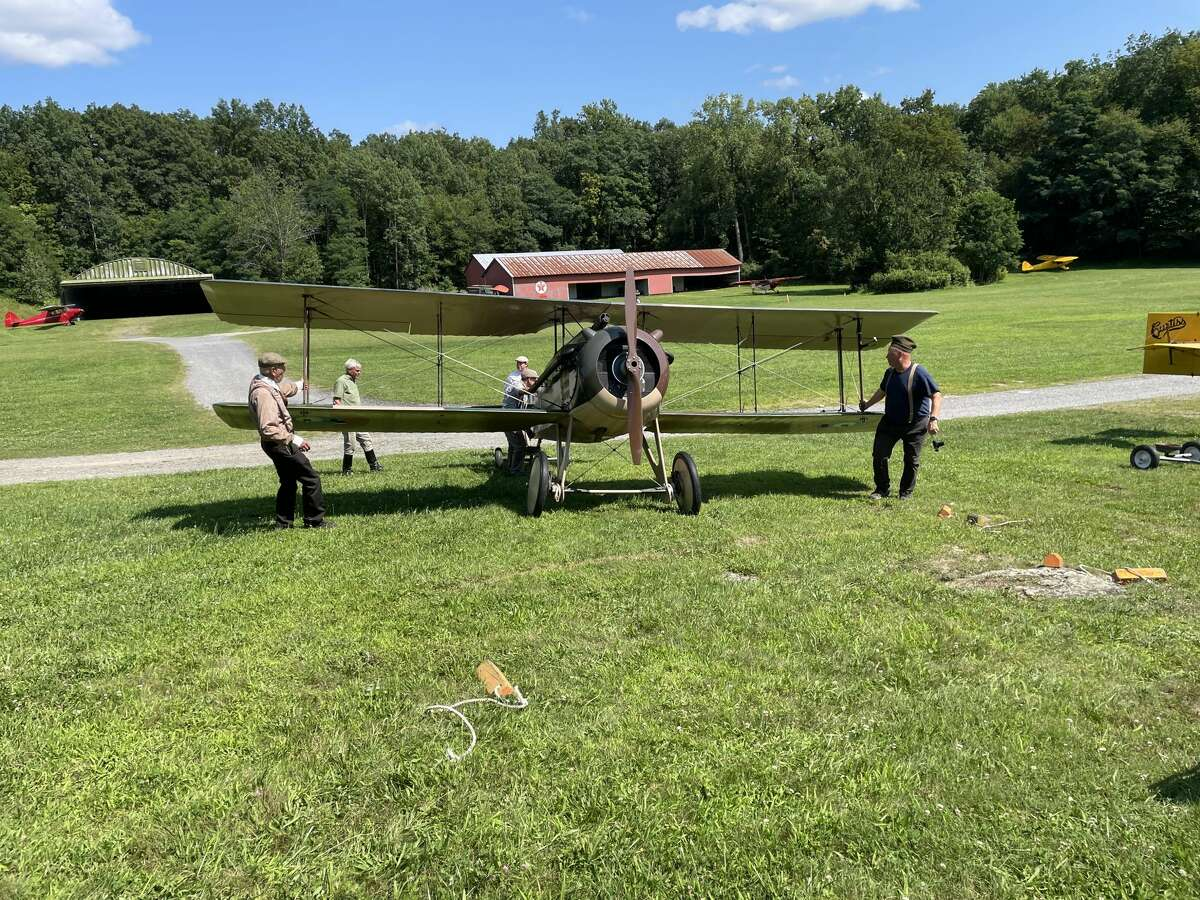 """A ground crew, wearing suspenders and khaki pants, pulls one of the vintage planes set to fly the """"History of Aviation"""" show out onto the grass taxiway. They do not use a tractor, or even one of the many vintage automobiles on site, they simply push and turn the plane out by hand and prepare it to taxi."""