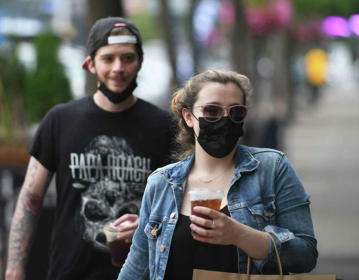 Stamford residents Matt Bonaiuto and Samantha Kraftsow put on their masks before entering a restaurant on Bedford Street in Stamford, Conn. Tuesday, Aug. 10, 2021. As of Thursday, Mayor David Martin reinstated the mask mandate requiring residents to wear masks indoors or at any outdoor events held on city property with more than 100 attendees.