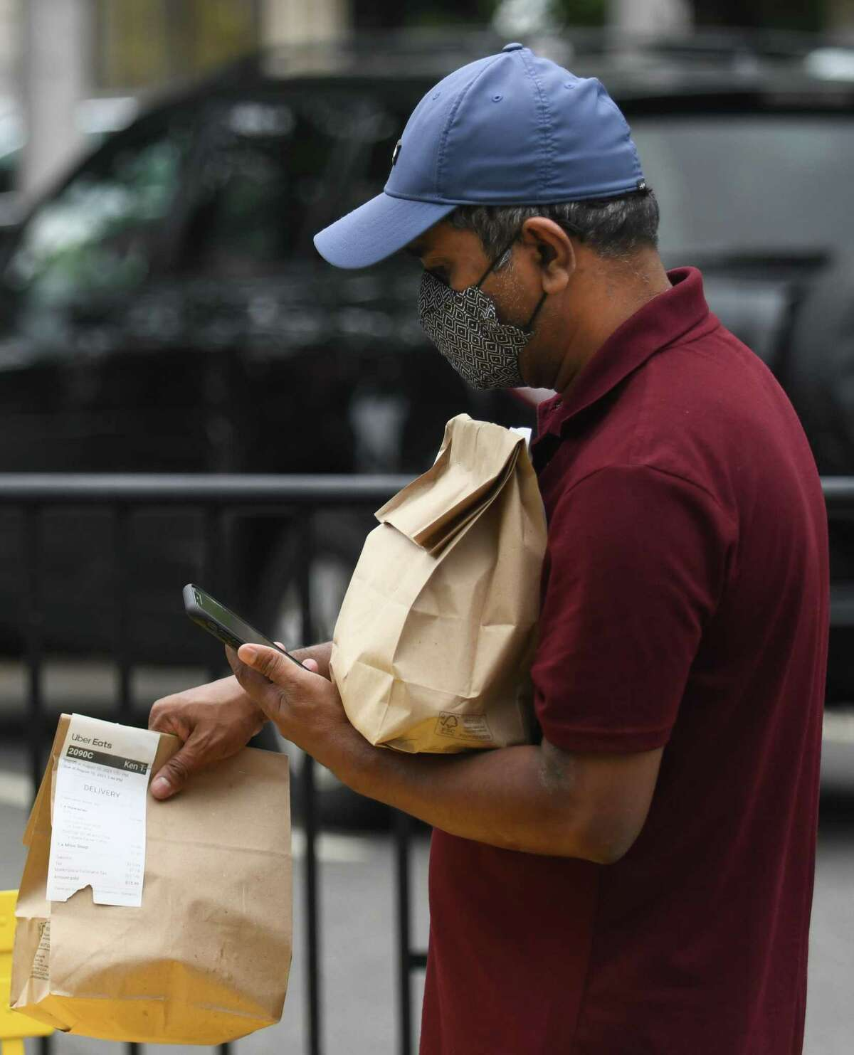 Uber Eats driver MD Hossain wears a mask while handling customers' delivery orders outside Fin II Japanese restaurant in Stamford, Conn. Tuesday, Aug. 10, 2021. As of Thursday, Mayor David Martin reinstated the mask mandate requiring residents to wear masks indoors or at any outdoor events held on city property with more than 100 attendees.