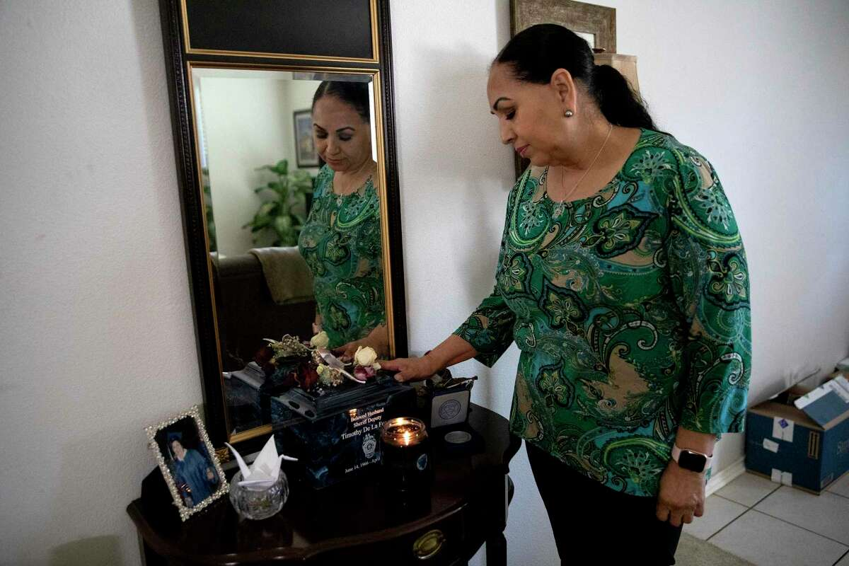 Pauline Pezina De La Fuente looks at reminders of her husband, Deputy Timothy De La Fuente, who died last year of COVID-19. She has been fighting Bexar County to receive death benefits for her husband, who she believes contracted the coronavirus on the job.