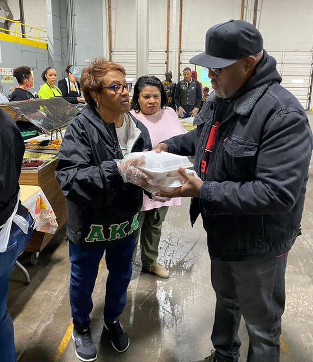 Upsilon Phi Omega members Adele Carpenter handing off a meal for the sick and shut-in at Soup N Share/Thanksgiving Day. Granite City on Nov. 28, 2019.