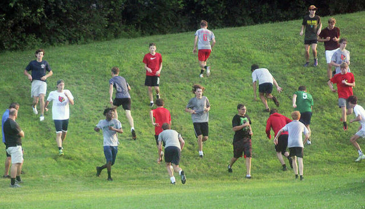 Alton soccer players run a steep hill during early morning practice Tuesday at AHS. The Redbirds practiced at AHS from 6 a.m. to 7:30 a.m. and again from 6 p.m. to 7:30 p.m. at Public School Stadium.