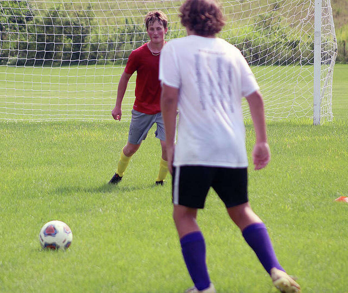 Civic Memorial's Brock Barrows (in red) waits for a pass from teammate Dylan Hoffman during a practice session at the Bethalto Sports Complex.