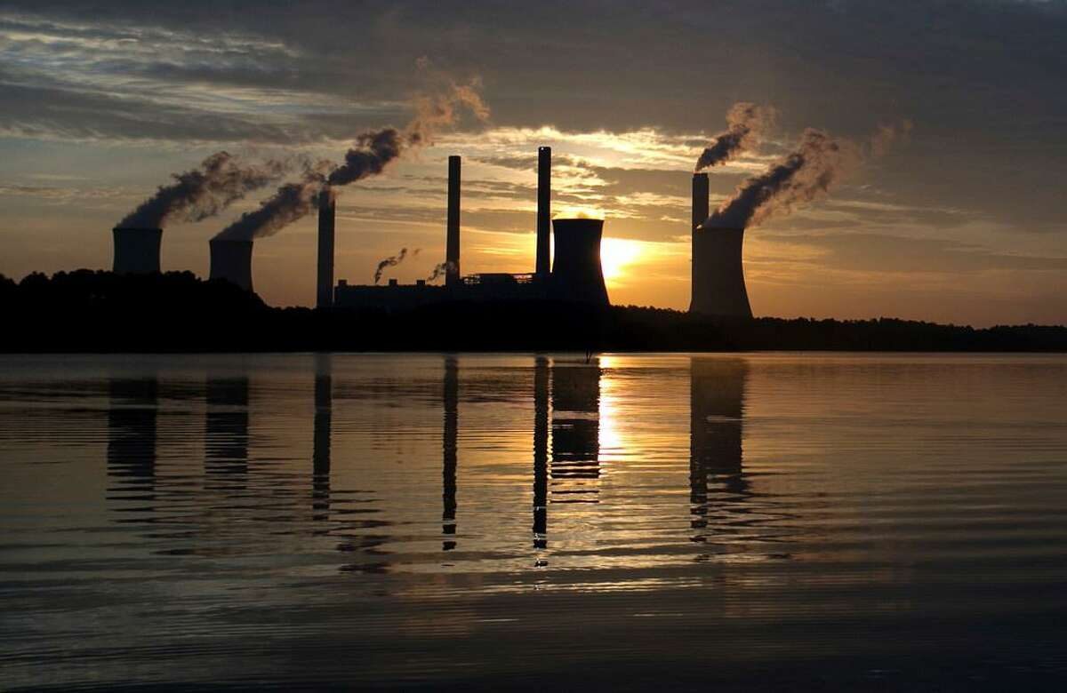 In this June, 3, 2017, file photo, the sun sets behind Georgia Power's coal-fired Plant Scherer, one of the nation's top carbon dioxide emitters, in Juliette, Ga. As climate change becomes a hotter topic in American classrooms in 2019, some politicians are pushing back against the scientific consensus that global warming is real and man-made.