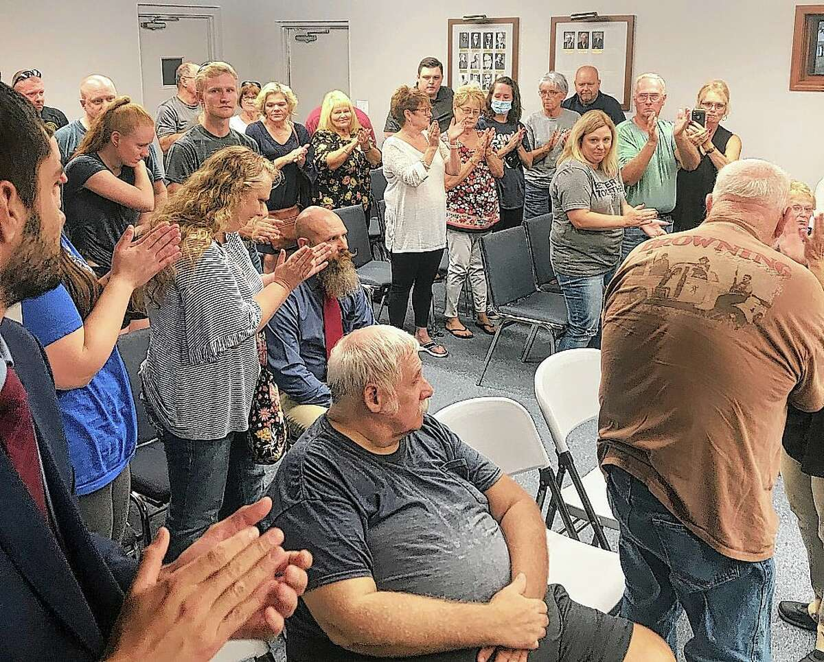 The audience gives South Jacksonville Police Chief Eric Hansell a standing ovation Monday evening after South Jacksonville trustees voted to overturn Hansell's termination.