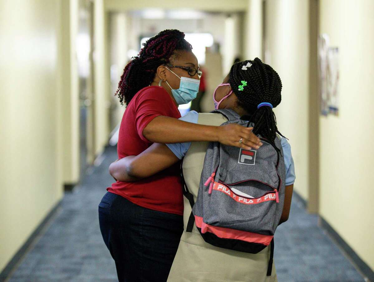 Chandra Hutto, Heflin Elementary librarian, greets a student on the first day of school on Tuesday, Aug. 10, 2021, in Houston.