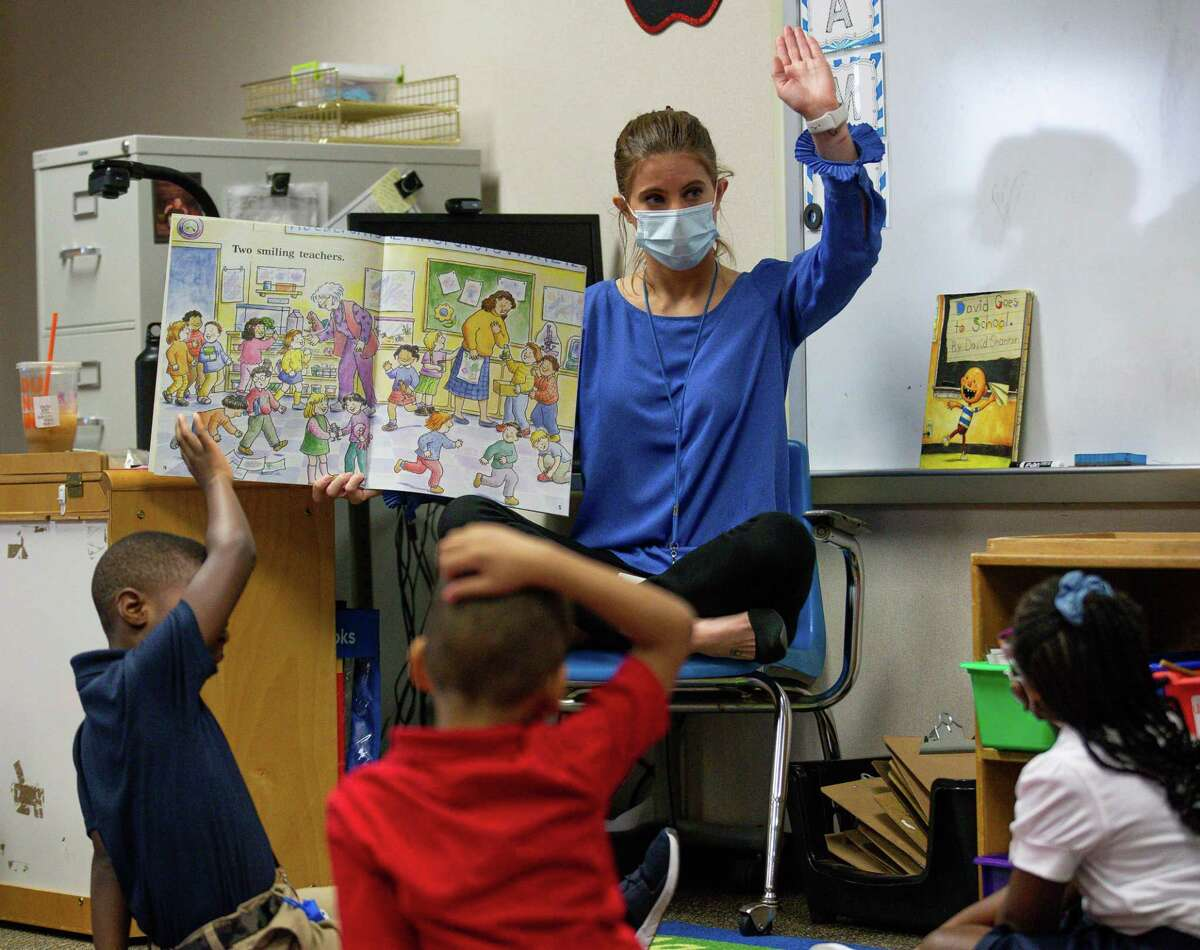 Heflin Elementary kindergarten teacher Lauren Fendley, center, reads a book with her students during the first day of school on Tuesday, Aug. 10, 2021, in Houston.