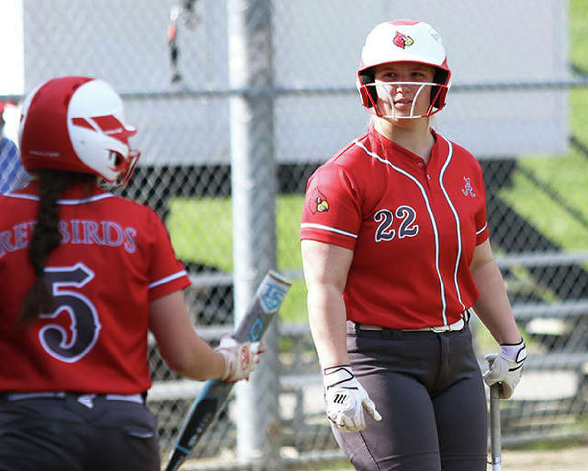 Alton senior Lynna Fischer (right) looks back to Audrey Evola before an at-bat during a game last season at Alton High in Godfrey. Fischer is the 2021 Telegraph Large-Schools Softball Player of the Year.