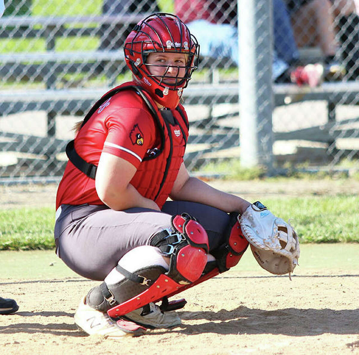 Alton catcher Lynna Fischer looks to the dugout for a pitch sign during a game last season at AHS in Godfrey. Fischer led the SWC in homers and slugging percentage as a senior.