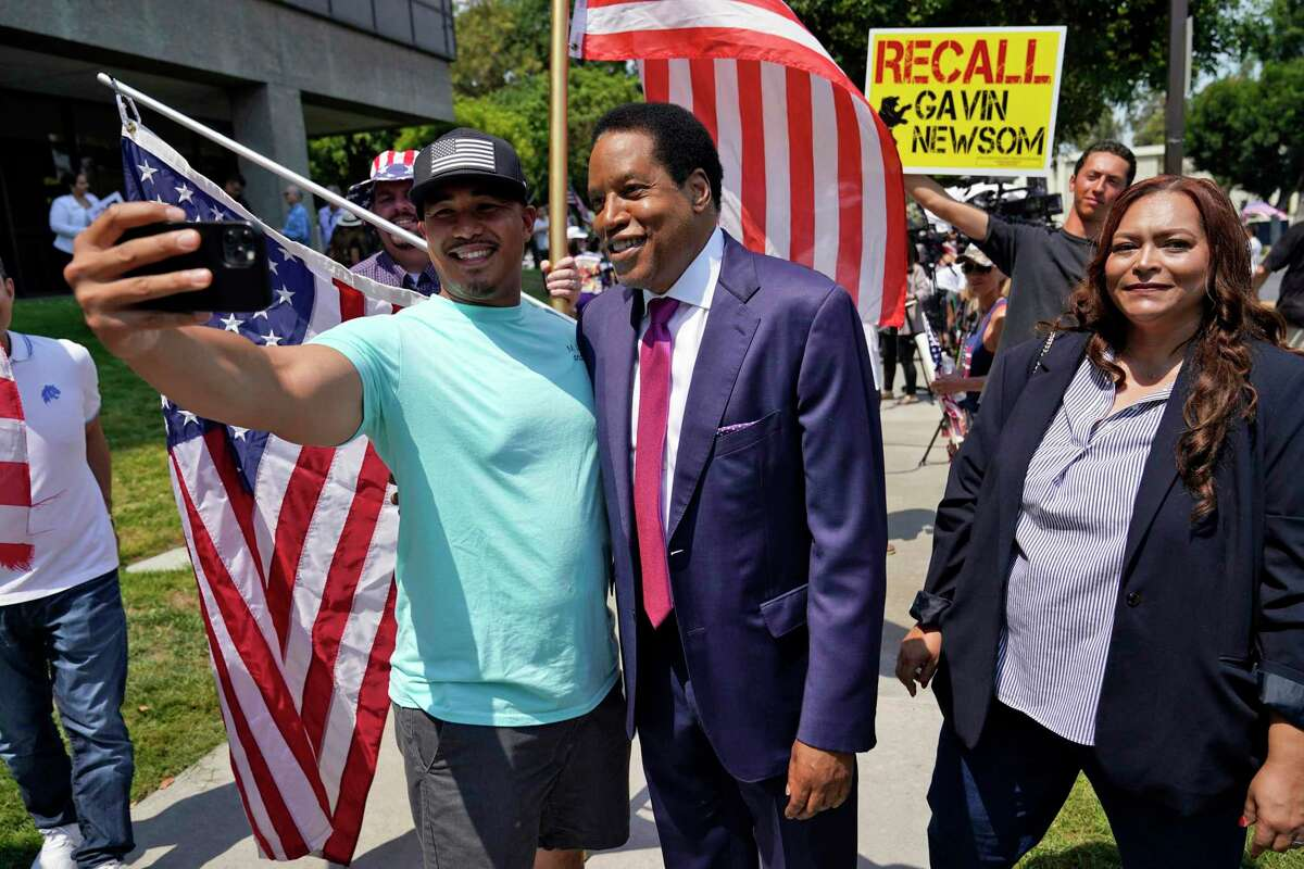 Radio talk show host Larry Elder, center, poses for selfies with supporters during a campaign stop Tuesday, July 13, 2021, in Norwalk, Calif.
