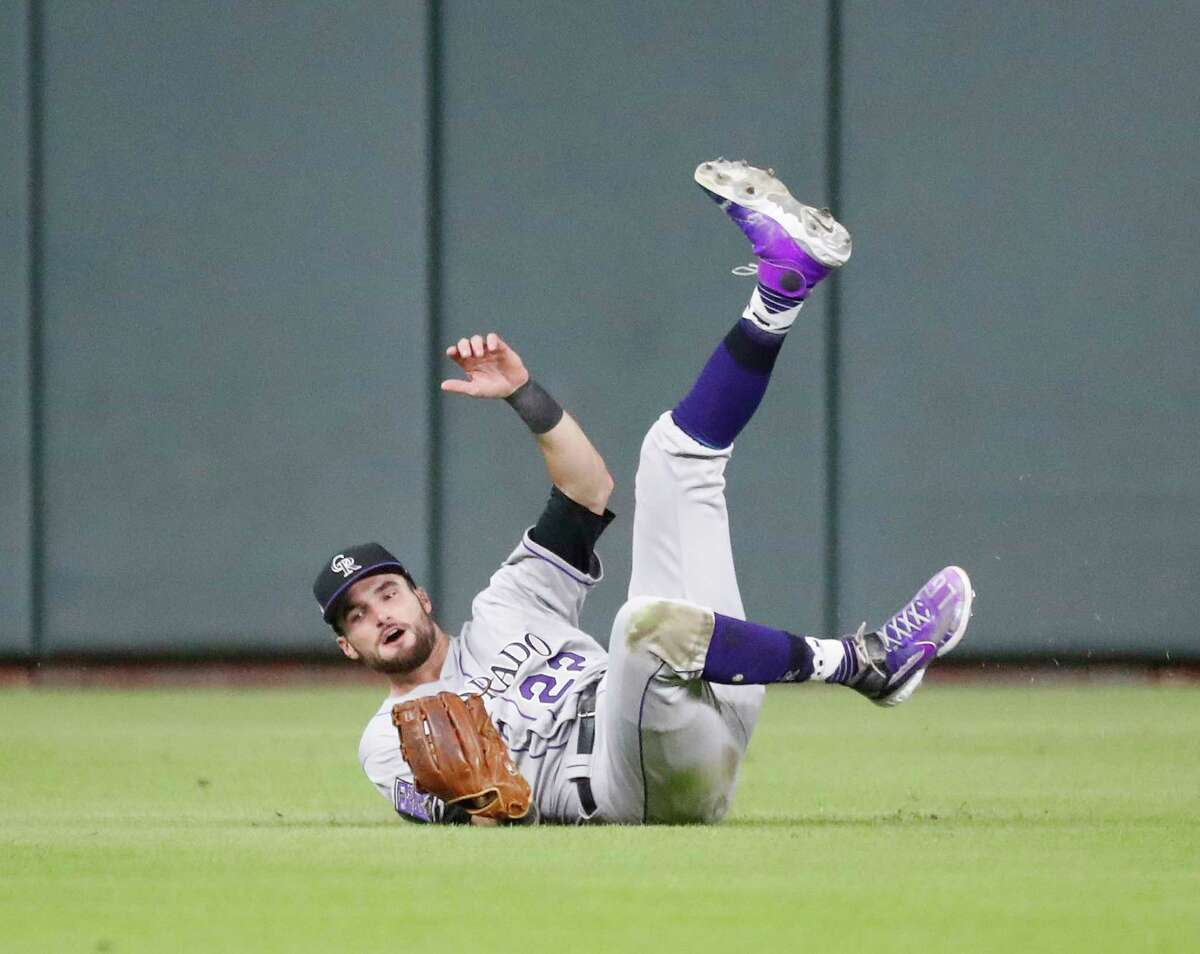 Colorado Rockies center fielder Sam Hilliard (22) dives to catch Houston Astros Jose Altuve's fly out during the first inning of an MLB baseball game at Minute Maid Park, Tuesday, August 10, 2021, in Houston.