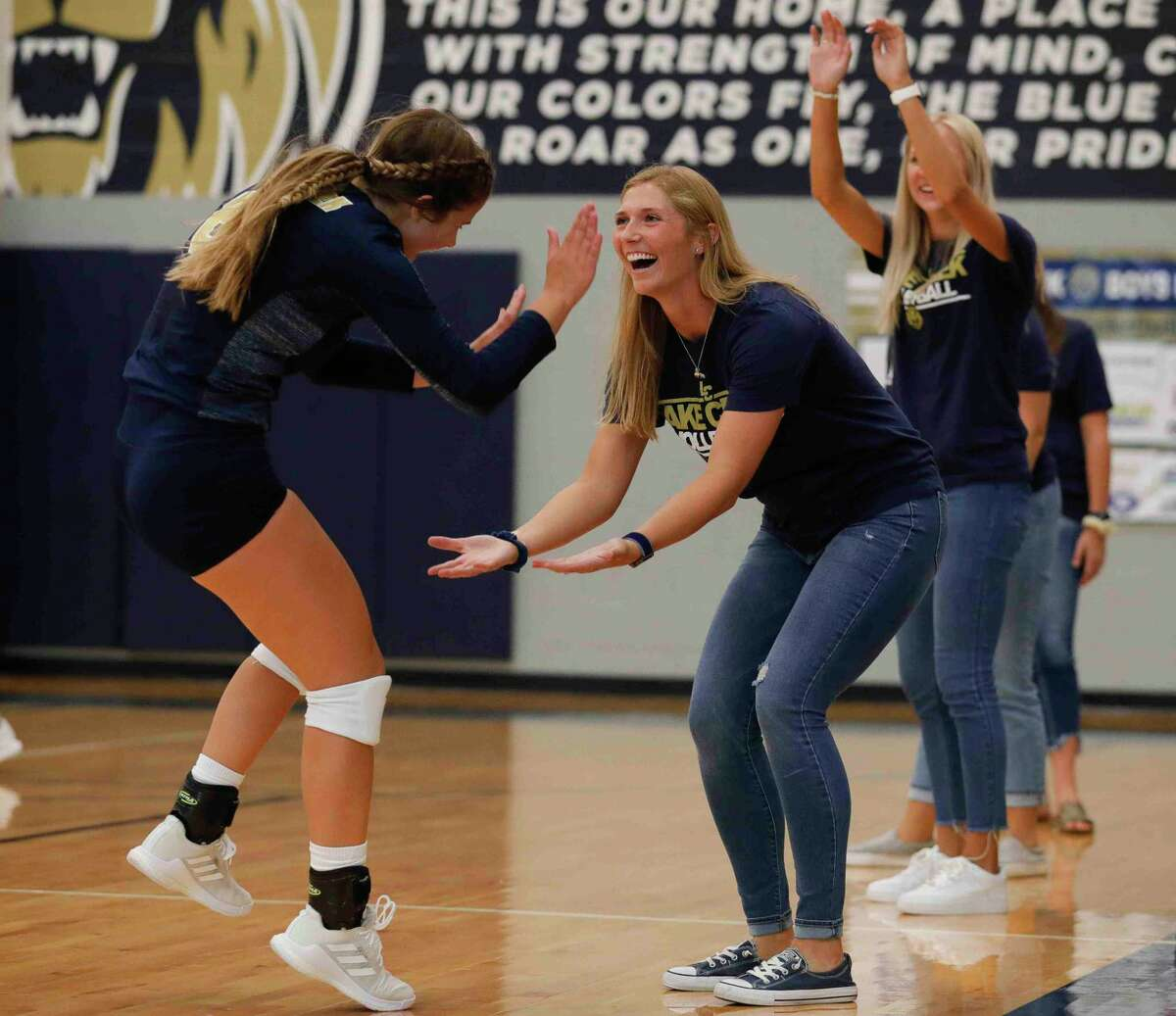 Lake Creek head coach Taryn Driver gives a high-five to Tyson Menville before the first set of a non-district high school volleyball match at Lake Creek High School, Tuesday, Aug. 10, 2021, in Montgomery.