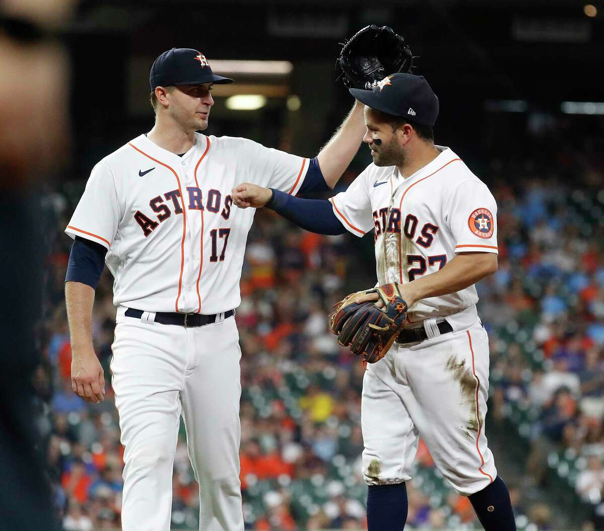 Houston Astros starting pitcher Jake Odorizzi (17) celebrates with Jose Altuve (27) after Altuve made the throw to first base from his knees as Colorado Rockies Connor Joe ground out to end the top of the fifth inning of an MLB baseball game at Minute Maid Park, Tuesday, August 10, 2021, in Houston.