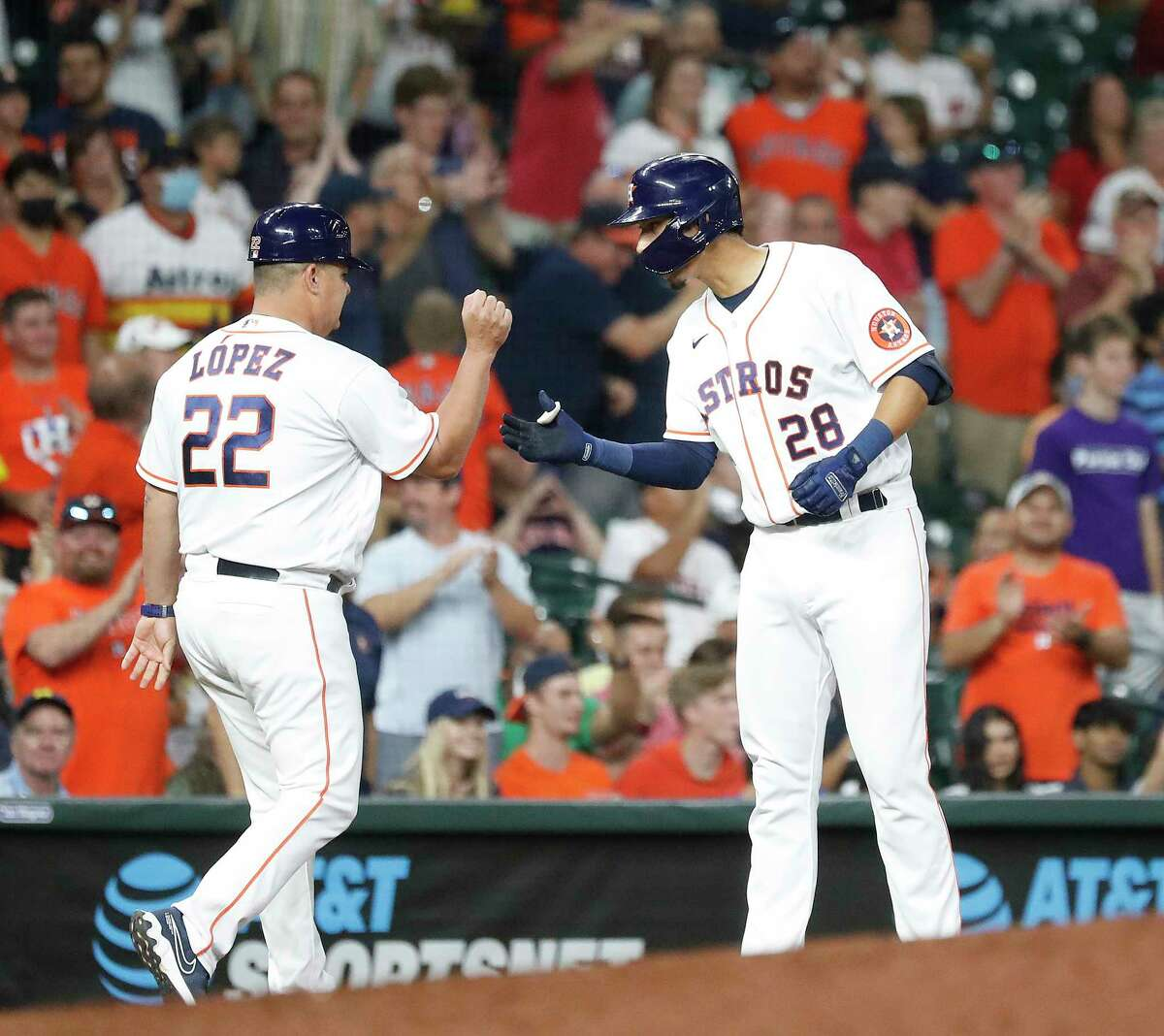 Houston Astros Taylor Jones (28) celebrates with third base coach Omar Lopez (22) an RBI double off Colorado Rockies starting pitcher Jon Gray, and due to a throwing error was able to reach third base during the fourth inning of an MLB baseball game at Minute Maid Park, Tuesday, August 10, 2021, in Houston.