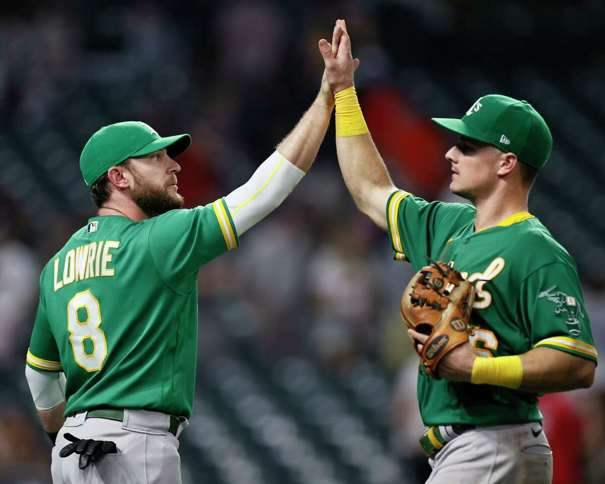 CLEVELAND, OH - AUGUST 10: Jed Lowrie #8 and Matt Chapman #26 of the Oakland Athletics celebrate a 4-3 victory over the Cleveland Indians in 10 innings at Progressive Field on August 10, 2021 in Cleveland, Ohio. (Photo by Ron Schwane/Getty Images)