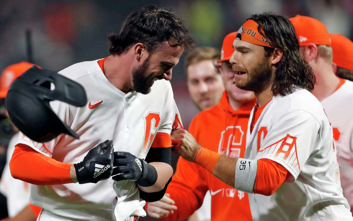San Francisco Giants' Kris Bryant celebrates with Brandon Crawford after the Arizona Diamondbacks' Christian Walker committed an error on a Bryant grounder giving the Giants an 8-7 win in MLB game at Oracle Park in San Francisco, Calif., on Tuesday, August 10, 2021.