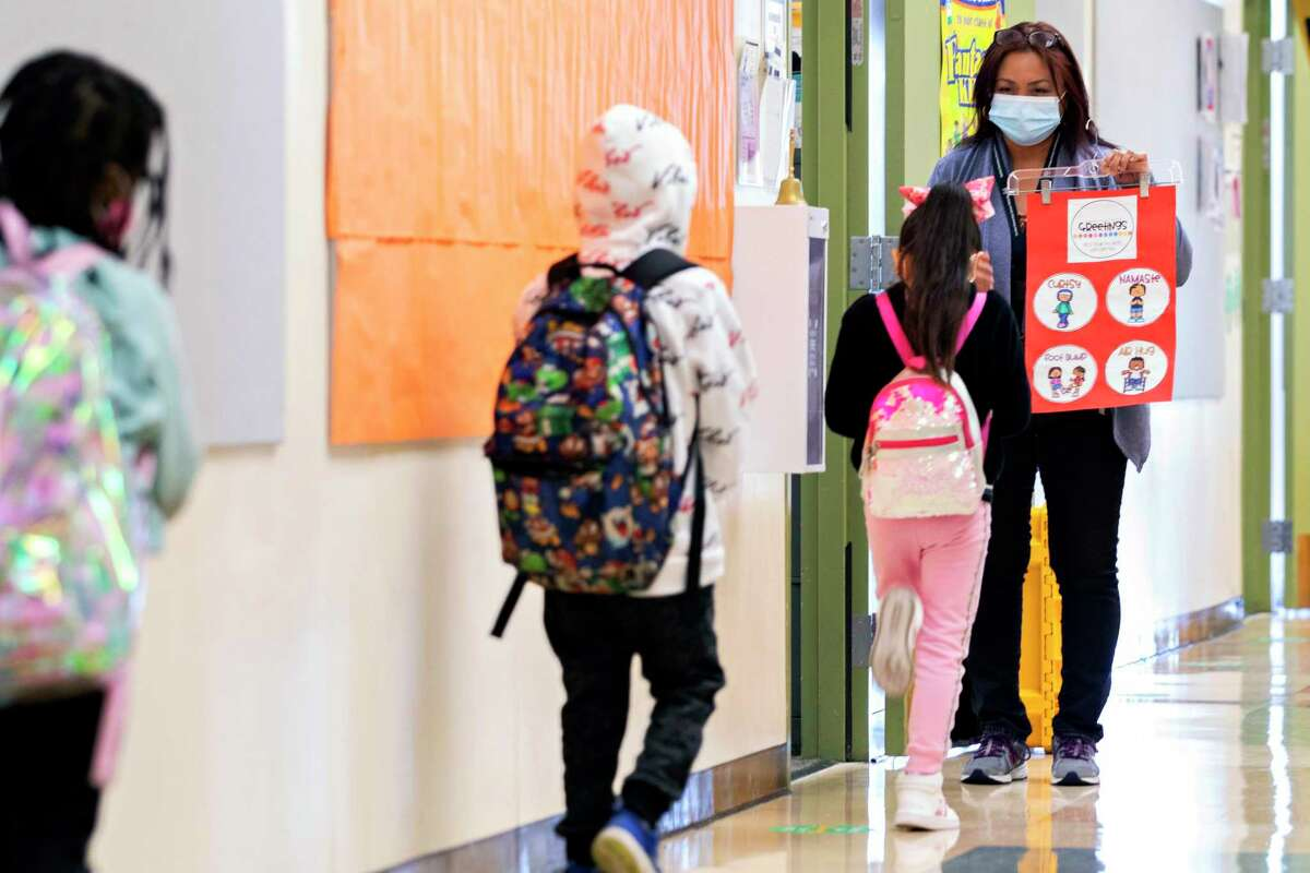 First grade teacher Johanna Taimanao greets her students at Garfield Elementary School in Oakland, Calif. Monday, April 19, 2021 during the first day of partial school-wide, in-person learning.