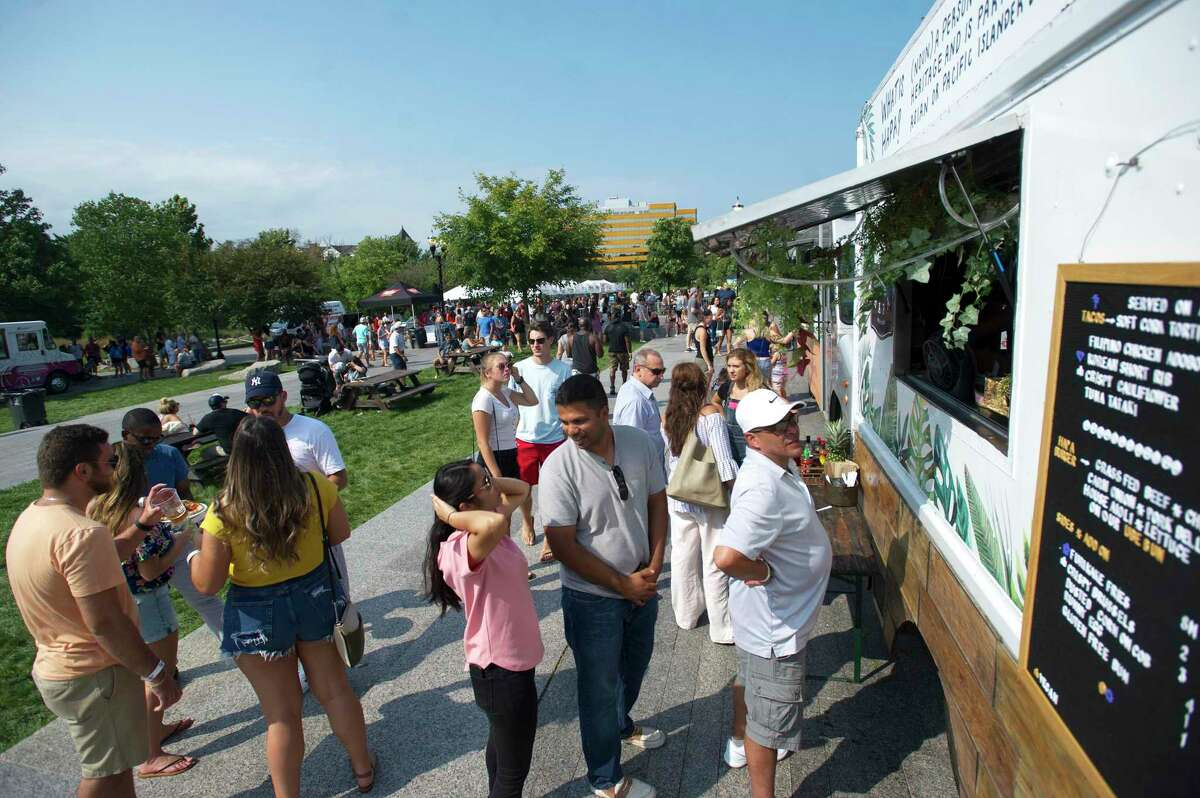 Food lovers wait in line at one of the more than two dozen food trucks at the second annual Hey Stamford! Food Fest in Mill River Park in 2018. This year, masks will be required during the outdoor event.