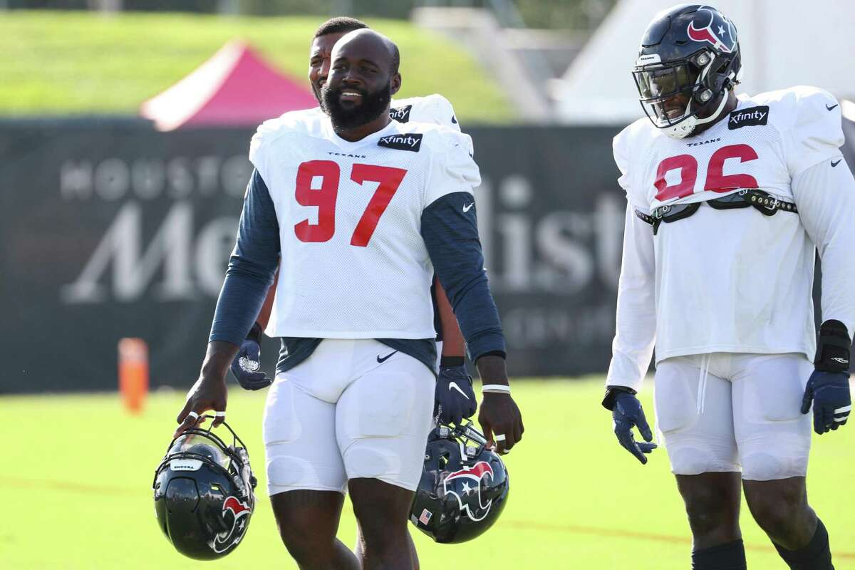 Houston Texans defensive tackles Maliek Collins (97) and Vincent Taylor (96) walk onto the field during an NFL training camp football practice Tuesday, Aug. 10, 2021, in Houston.